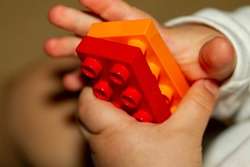 Close up image of an infant baby's hands as he or she is trying to interlock two toy bricks. Image is useful to demonstrate motor development, fine motor skills, balance, precision, baby growth themes