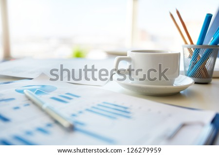 Close-up image of an office desk at morning with a cup of tea and financial documents #126279959