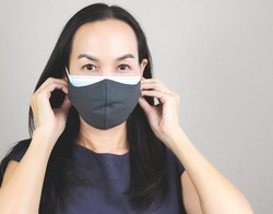 Close up image of Asian woman wearing  double face masks  or two face masks for better protection  from coronavirus or covid-19 outbreak - concept of safety, healthcare, medical and hygiene.