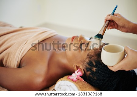 Close-up image of beautician applying deep clearing clay mask on face of Black young woman Photo stock ©