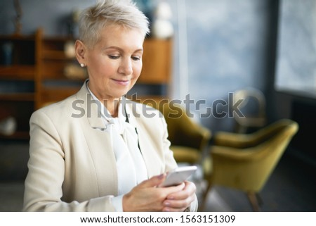 Close up image of beautiful confident mature businesswoman sitting at her office typing text message using online messenger on mobile phone or scrolling newsfeed via social network, smiling stock photo