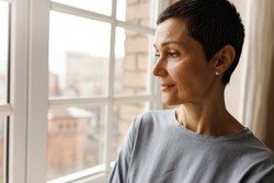 Close up image of beautiful short haired mature female with face wrinkles relaxing indoors, standing by window, daydreaming, having thoughtful look. Attractive retired woman spending time at home