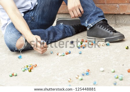 Close-up image of boy's hand playing marbles on the street