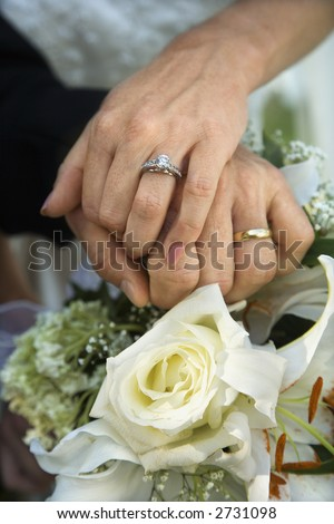 Close up image of bride and groom\'s hands overlapping.