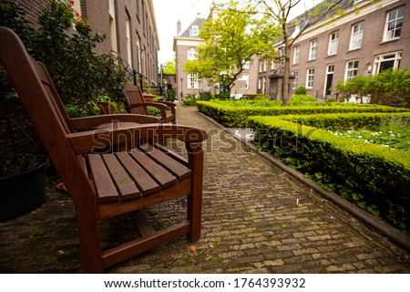 Close up image of brown red wooden chairs on one side of a courtyard garden in a senior housing community. In the background there is  a well maintained garden, brick buildings and cobblestone ground.