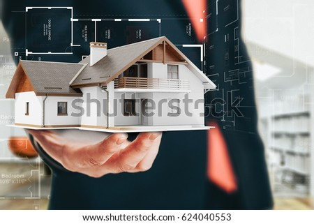Close-up image of businessman holding a 3d house, architecture project