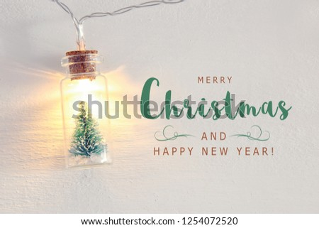 close up image of Christmas tree in the masson jar garland light over wooden white background