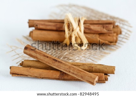 Close up image of cinnamon sticks on a white cover.