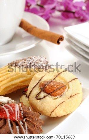 Close-up image of cookies with coffee and cinnamon stick on white background