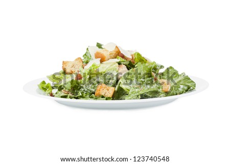 Close up image of delicious ceasar salad in white plate against white background