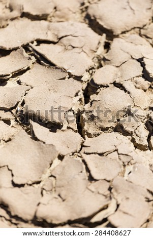 Close up image of dry and cracked clay in an old riverbed in the hot african sun. To be used for textures or backgrounds.
