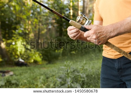 Close up image of elderly man's hands with wrinkles holding fishing rod. Cropped picture of unrecognizable senior mature male fishing on river bank, standing against green trees background