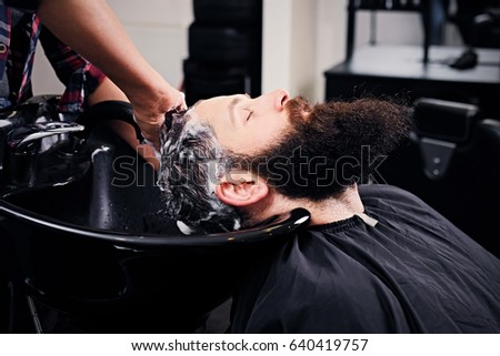 Close up image of female hairdresser washing bearded men's hair before haircut in a saloon. #640419757
