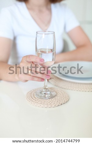 close up image of female hand holding glass of water. Champaign glass standing on handmade knitted crochet serviette table napkin Stock photo ©