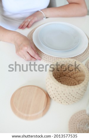 close up image of female hands arranging handmade knitted table serviette on dinner table.  Stock photo ©