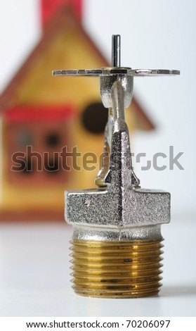 Close up image of fire sprinkler on white. Fire sprinklers are part of an integrated water piping system designed for life and fire safety.  Replica of house added to background.