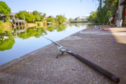 Close up image of fishing rod on cement fishing pier at river shore with blur background of trees and local wooden houses by the riverbank of Chanthaburi river in Chanthaburi province east of Thailand