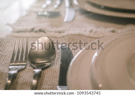 Close-up image of fork and spoon with knife arranged beside a white ceramic plate. #1093543745