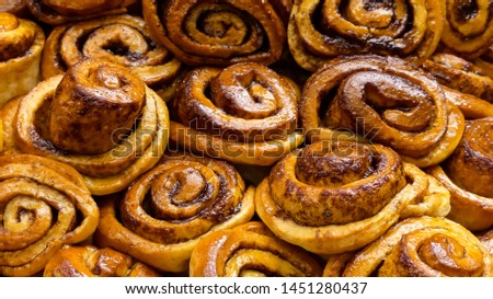 Close up image of freshly  handmade cinnamon swirls in natural light. With glistening glazed tops. A collection, each, individual with variations in colours, shapes and textures. Abstract landscape #1451280437