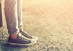 close up image of girl in sneakers sitting on the bench.