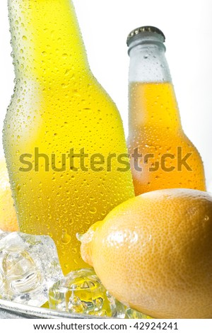 Close up image of glass bottles with water drops in bucket with ice cubes and fresh lemon