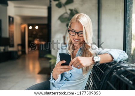 Close-up image of gorgeous blonde woman texting indoors. #1177509853
