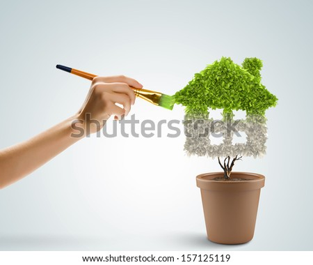 Close up image of hand painting plant shaped like house