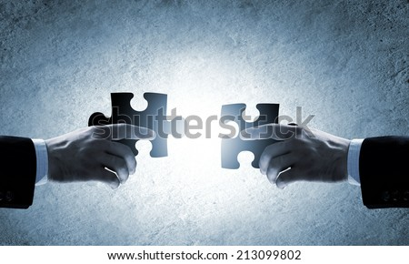 Close up image of hands connecting puzzle elements