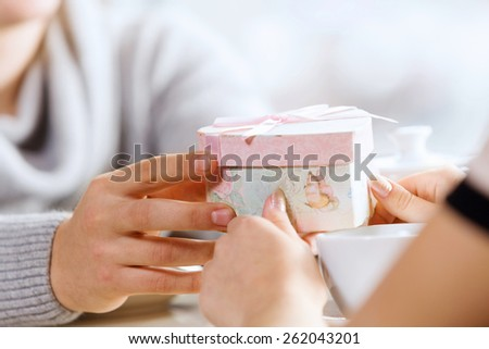 Close up image of hands presenting a box with surprise