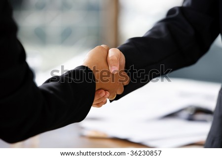close up image of handshake between two businesswomen. Different skin tones