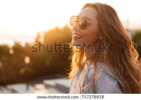 Close up image of happy brunette woman in sunglasses and autumn clothes posing sideways outdoors