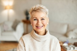 Close up image of happy good looking elegant fifty year old woman wearing warm cozy jumper, pearl earrings and short stylish hairdo being in good mood sitting in living room, smiling broadly at camera