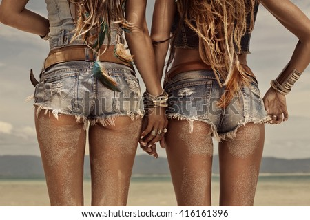 Stock Photo Close up image of hippie girls buttocks wearing denim shorts