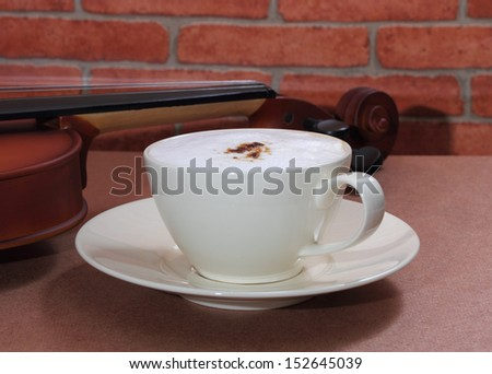 close up image of hot coffee and white cup with violin in coffee shop