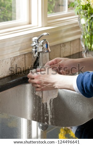 Close up image of human hand washing dish cloth