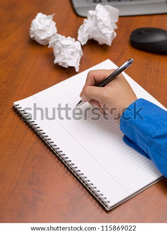 Close-up image of human hand writing on spiral writing pad on wooden office desk with crumpled papers.