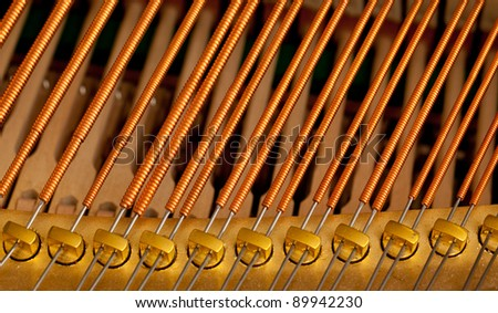 Close up image of interior of grand piano showing strings and structure