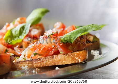 Close-up image of italian bruschetta with tomatoe and basil on a serving plate