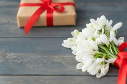 Close up image of little gentle bouquet of white snowdrops with red ribbon, wrapped gift box on dark wooden background. Copy space for text. Spring holidays, greetings concept.