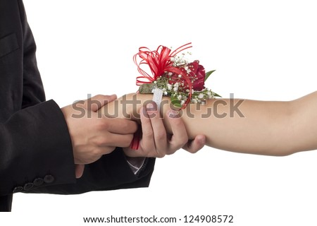 Close-up image of male hand holding female hand with corsage isolated on a white background