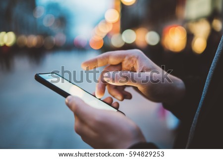 Close-up image of male hands using smartphone at night on city shopping street, searching or social networks concept, hipster man typing an sms message to his friends #594829253