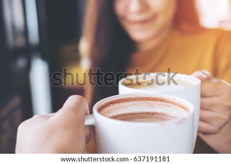 Close up image of man and woman clink white coffee mugs in cafe