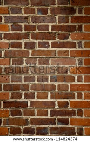 Close up image of Orange and brown brick wall.  concrete seperation between each brick is visible