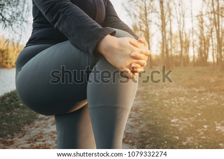 Close up image of overweight woman warming up legs before outdoor running. Jogging, sport, activity, healthy lifestyle and weight losing