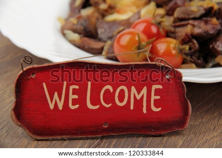 "Close up image of pasta with mushrooms and small tasty tomatoes with sign ""Welcome"""