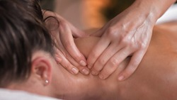 Close up image of physiotherapist massaging female patient with injured neck muscle. Sports injury treatment