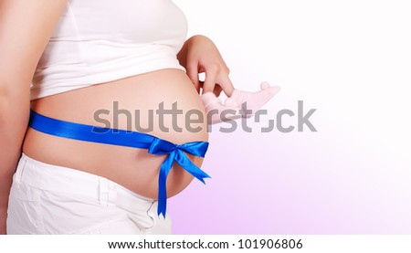 Close up image of pregnant woman tummy with blue ribbon and  baby's bootees