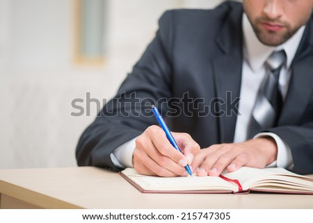 Close-up image of red notebook and hands of businessman sitting at the table in office with a pen attentively writing some notes with copy place