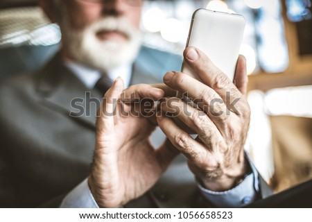 Close up image of senior businessman using mobile phone.  Focus on hand.  Stockfoto ©