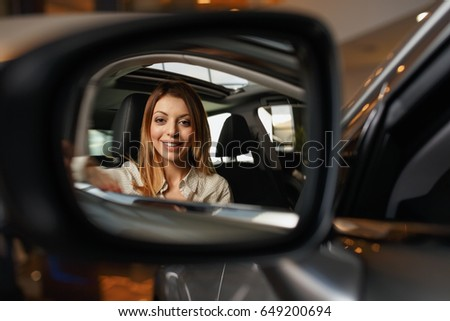Close-up image of side rear-view mirror with reflection of beautiful young woman sitting in car at dealership and smiling #649200694